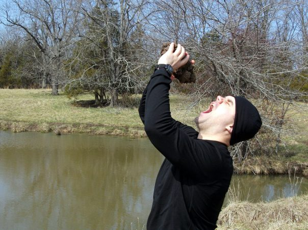 Luke as Bear Grylls squeezing water out of poop